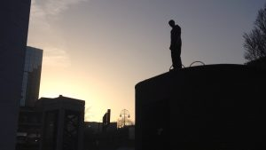 This picture shows a silhouette stood on a tall block on the right of the image, gazing down to the bottom-left which has a lower block. There is funky lighting in the sky.